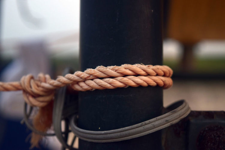 Close-up of rope tied to pole outdoors