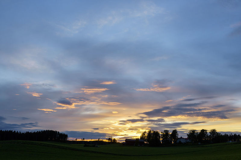 Scenic view of dramatic sky over field during sunset