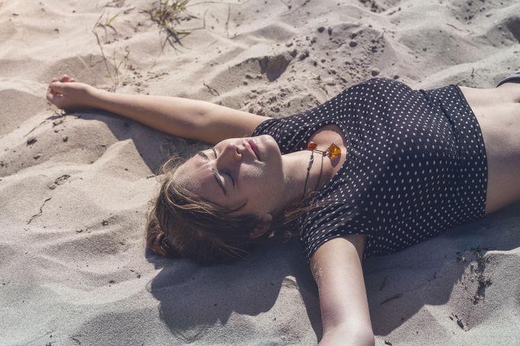 High angle view of woman lying on sand