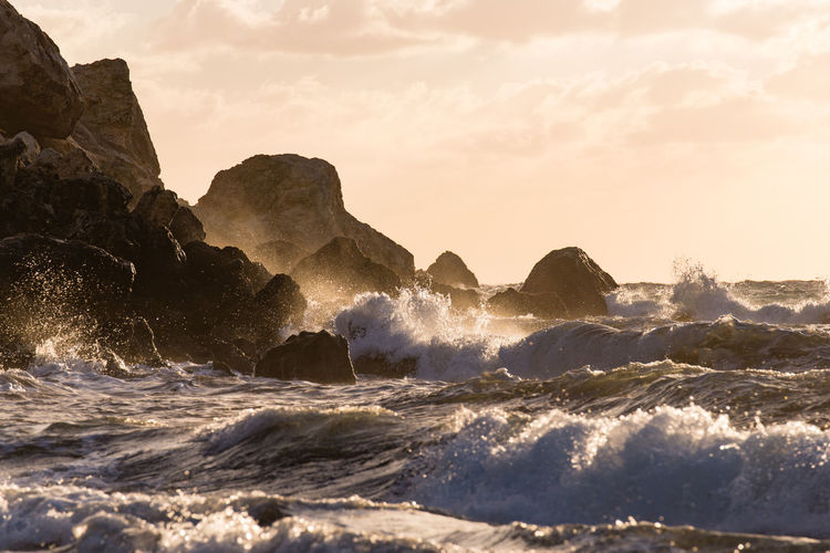 Waves splashing on rocks at shore against sky
