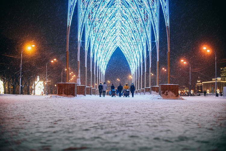 People walking on snow covered street at night