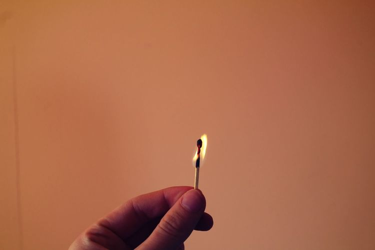 Cropped hand holding burning matchstick against brown wall