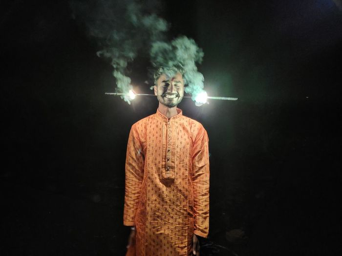 Man carrying illuminated sparkler in mouth