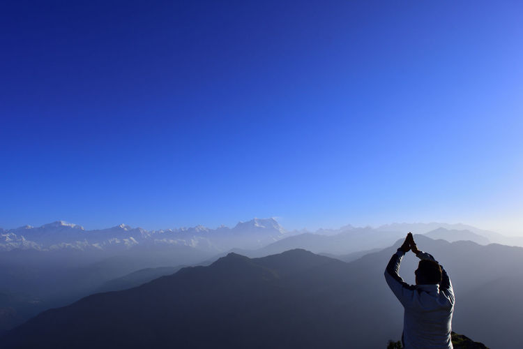 Rear view of man practicing yoga on mountain against clear blue sky