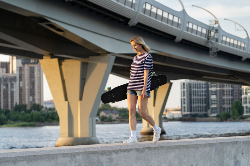 Full length of woman standing on bridge in city