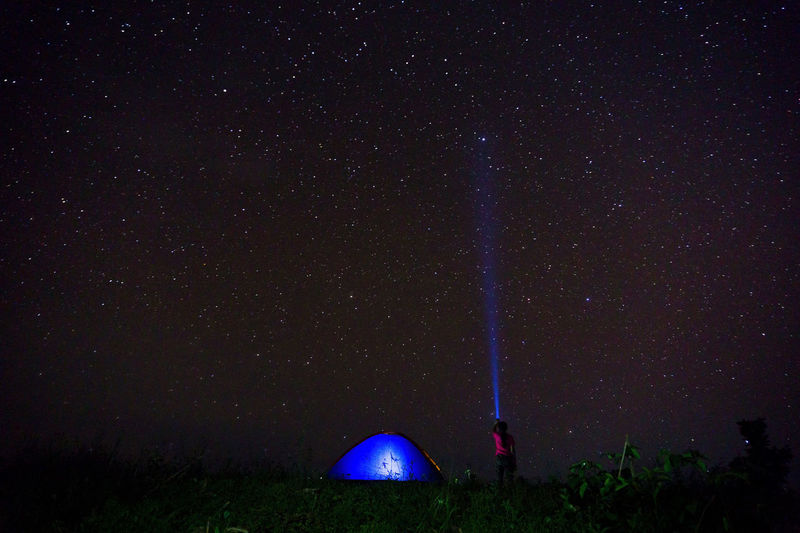 Woman with illuminated flashlight and tent against star field at night