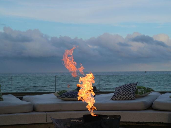 Fire on sea against sky
