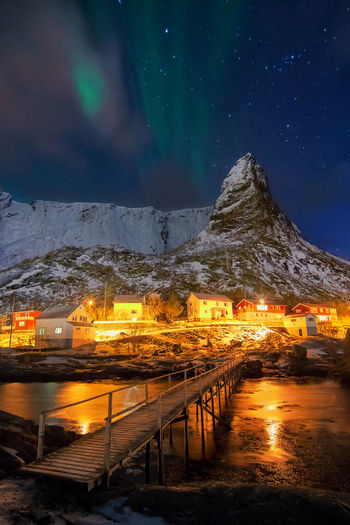 Wooden Bridge Over River Leading Towards Illuminated Houses And Mountain At Winter