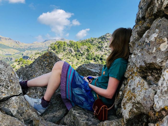 At the mountain EyeEm Selects Leisure Activity Lifestyles Real People One Person Women Day Rock - Object Mountain Casual Clothing Cloud - Sky Rock Nature Beauty In Nature Sunlight Outdoors Sky Hairstyle Sitting Solid Adult