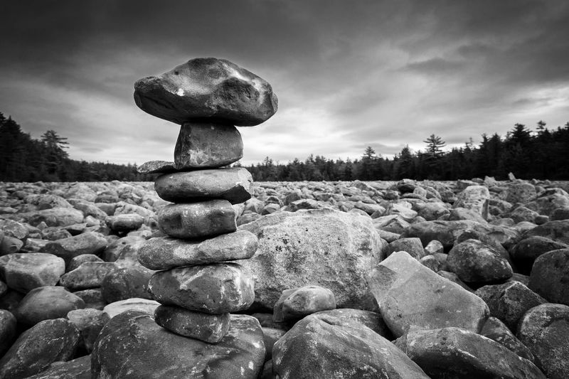 Stack of pebbles on rocks against sky