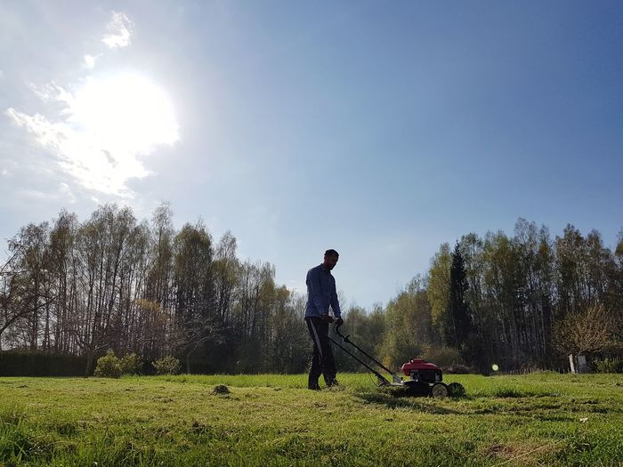 Man cleaning field with lawn mower against sky