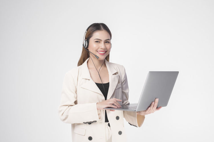Young woman using smart phone against white background