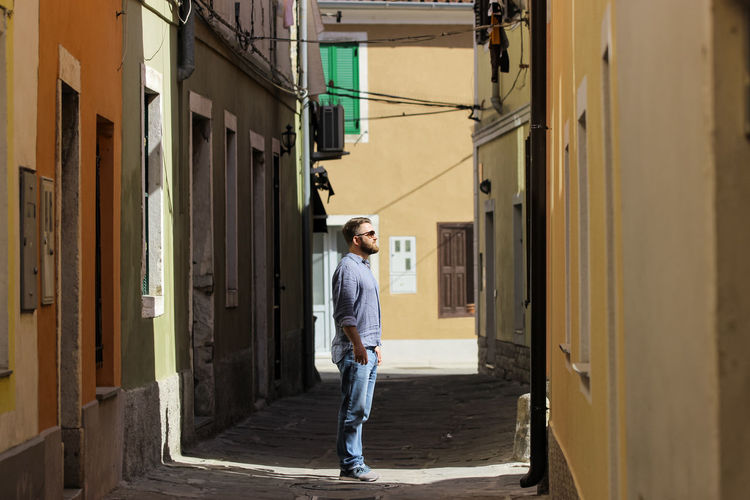 Man standing at alley amidst buildings in city