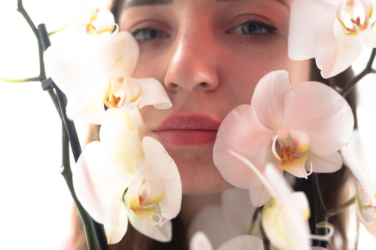 Close-up portrait of woman by flowering plant