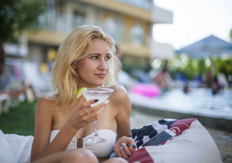 Young woman holding martini glass while sitting outdoors