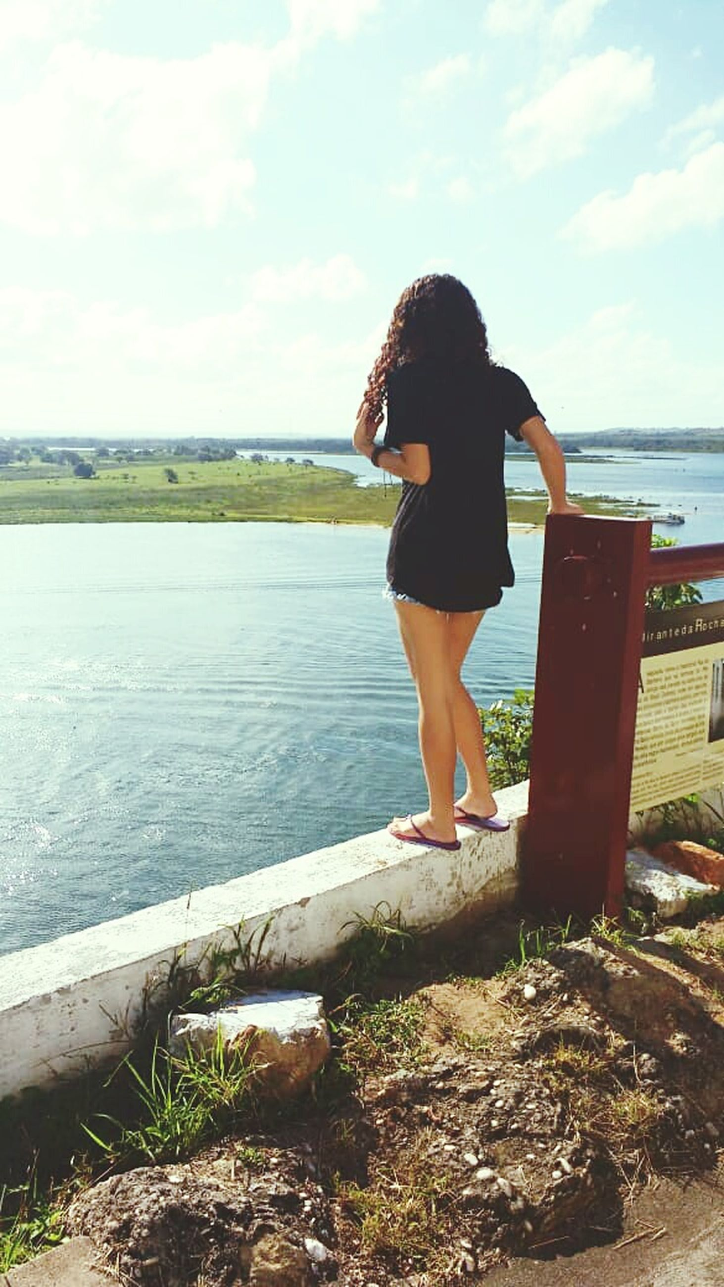 water, one person, sky, full length, leisure activity, nature, standing, real people, day, rear view, beauty in nature, lifestyles, women, sea, scenics - nature, young adult, casual clothing, adult, outdoors, hairstyle, looking at view