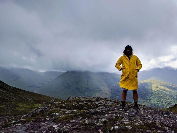 Man wearing raincoat while standing on mountain during rainy season