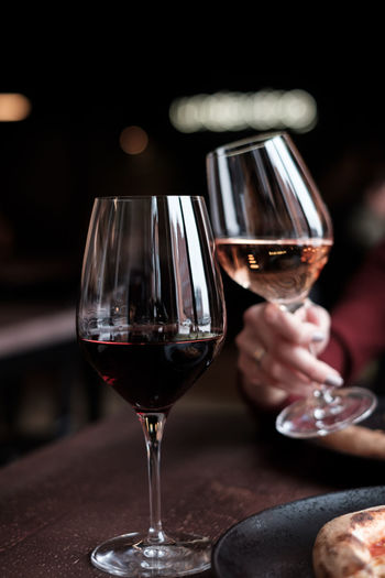 Toasting with glass of wine Glass Alcohol Drink Food And Drink Refreshment Wine Wineglass Red Wine Winetasting Transparent Glass - Material Close-up Freshness Indoors  Household Equipment Focus On Foreground Table Drinking Glass Human Body Part Luxury Drinking Hand
