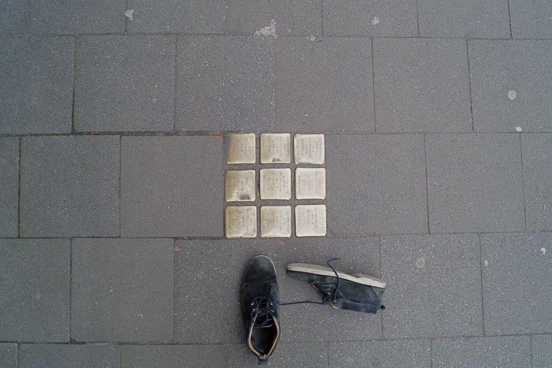 Question mark. These little quadrats/squares are so called Stolpersteine (stumbling blocks) that remind on victims of Nazi suppression. More Informations: https://en.wikipedia.org/wiki/Stolperstein Antifasisct Arrangement Cobblestone High Angle View Monument Q Shoe Shoes Sidewalk Stolpersteine Stumbling Block
