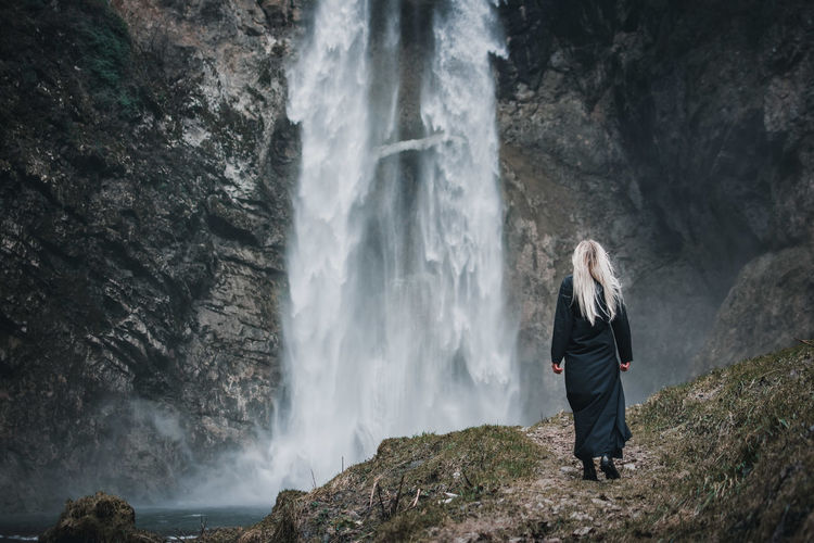 Woman standing on rock looking at waterfall
