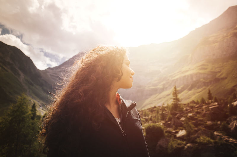 Young woman with curly hair enjoying the tranquility of the sunset in the dolomite mountains in Northern Italy Dolomites, Italy Freedom Travel Adult Beauty In Nature Environment Hair Hairstyle Leisure Activity Lifestyles Long Hair Mountain Mountain Range Nature One Person Optimism Outdoors Real People Scenics - Nature Sky Standing Sunset Women Young Adult Young Women