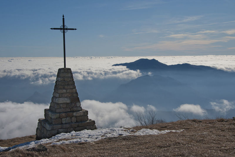 Cross on mountain against cloudscape