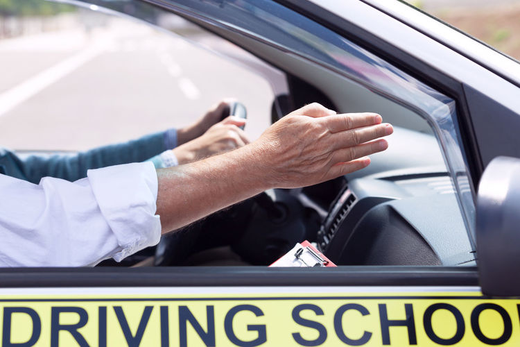 Cropped hand of instructor teaching driving in car