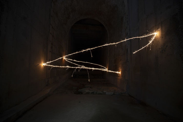 Low angle view of illuminated lights in tunnel at night