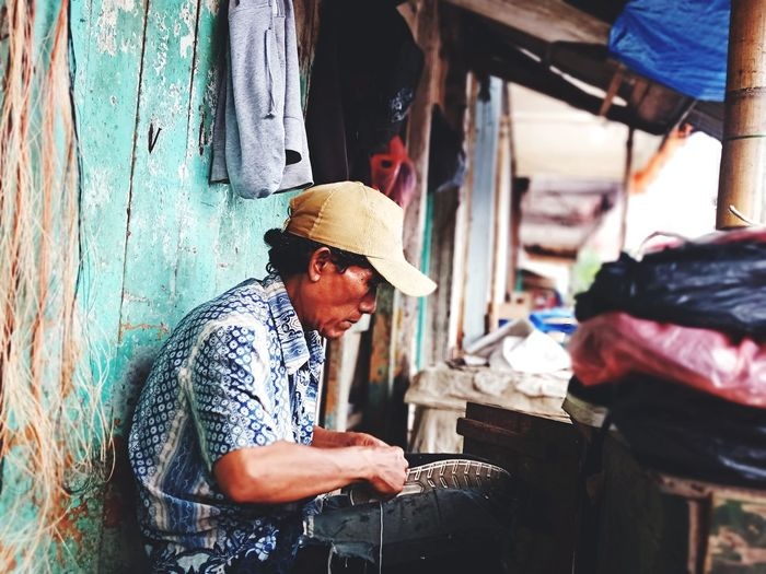 Side view of a man working on wood