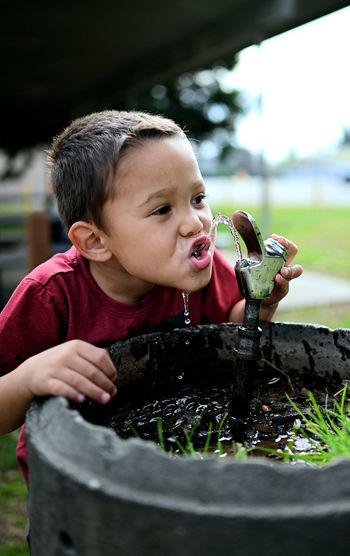 Portrait of boy drinking water