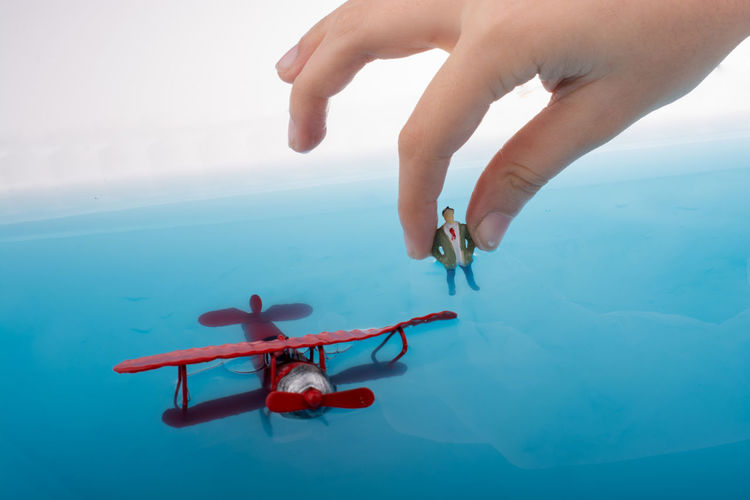 Close-up of person hand holding figurine by model airplane against sky