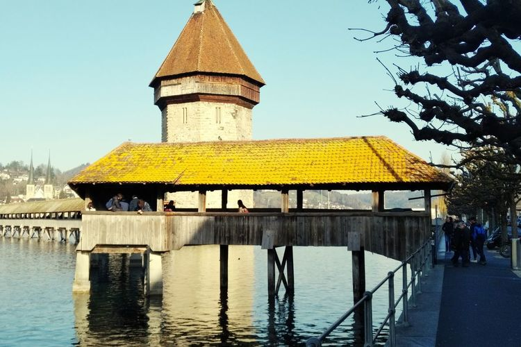 old wood bridge in Luzern. #Rauchenverboten Wood Woodbridge Tower Bridge  Oldcity Symmetrical Symmetrie Vivid Vivid Colours  Vividmoments Blue Sky Blueskiesandsunshine Spring Springtime Spring Has Arrived Spring Colours City Yellow Water History Sky Architecture Building Exterior Built Structure Calm Waterfront Mid Distance Standing Water Lake Lakeside