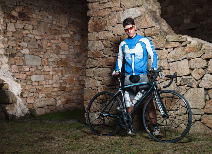Full length of man with bicycle standing against stone wall