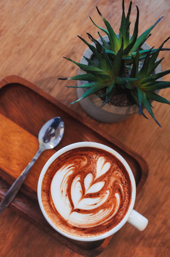 Hot Coffee on wooden table Drink Table Refreshment Coffee - Drink Food And Drink Coffee Still Life Frothy Drink Leaf Plant Part Cup Coffee Cup Mug Froth Art Cappuccino Indoors  Plant No People Hot Drink Wood - Material Crockery Latte Houseplant
