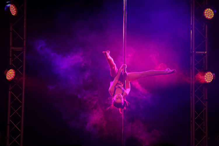 View of young woman pole dancing