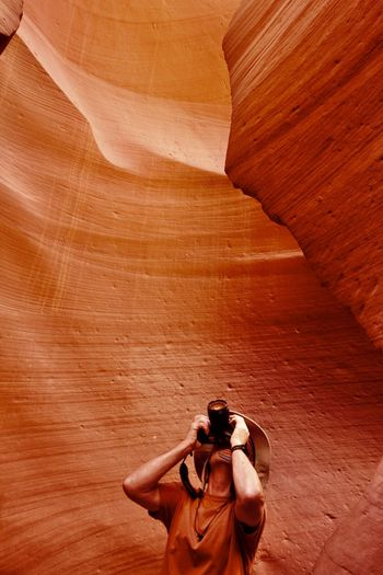 Man photographing amidst canyon