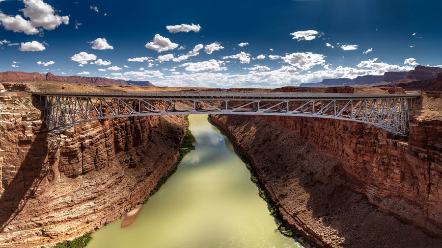 Navajo bridge over river against sky