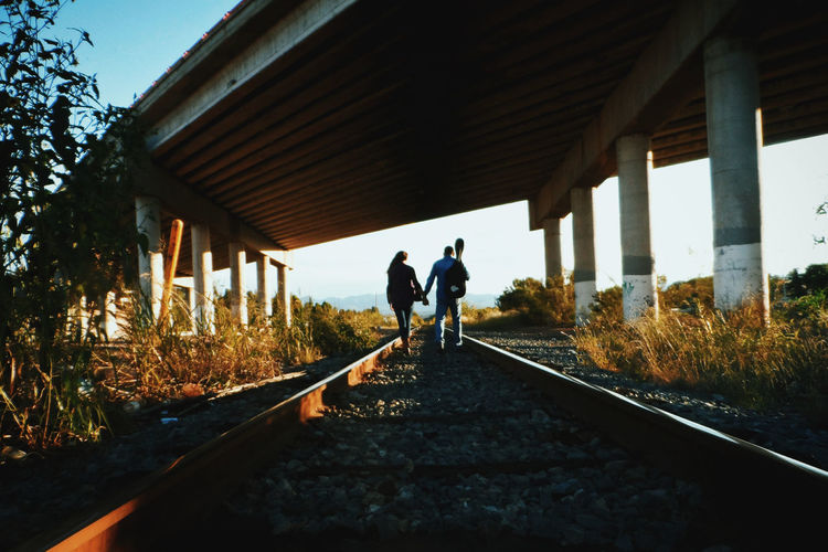 People Holding Hands While Walking On Railroad Track