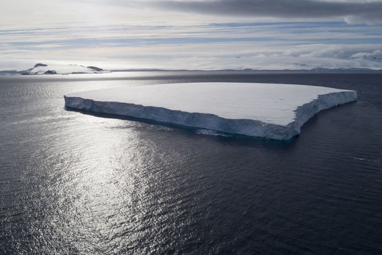 A tabular iceberg in Hope Bay on Trinity Peninsula, which is the northernmost part of the Antarctic Peninsula. Antarctic Antarctica Drone  Global Warming Melting Aerial Aerial View Beauty In Nature Beauty In Nature Climate Change Cold Temperature Horizon Ice Iceberg Landscape Nature No People Ocean Outdoors Scenics - Nature Sea Seascape Tabular Iceberg Tranquil Scene Water