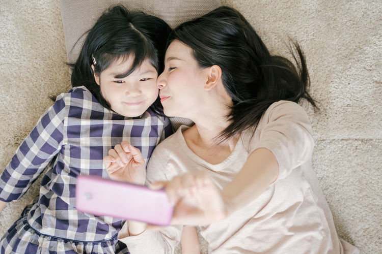 Mother is selfie with her little daughter using a smart phone camera while kissing daughter cheek Mom Mother Daughter Girl Girls Asian  Home Family Love Bed Bedroom Kiss Kissing Selfie Smart Phone Camera Phone Cheek Two People Togetherness Real People Women Females Black Hair Adult Bonding Young Adult Mobile Phone Connection Emotion Casual Clothing People Young Women Lifestyles Waist Up Indoors  Child Wireless Technology Positive Emotion Hair Hairstyle Sister