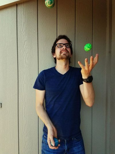 Man Juggling While Standing Against Wall