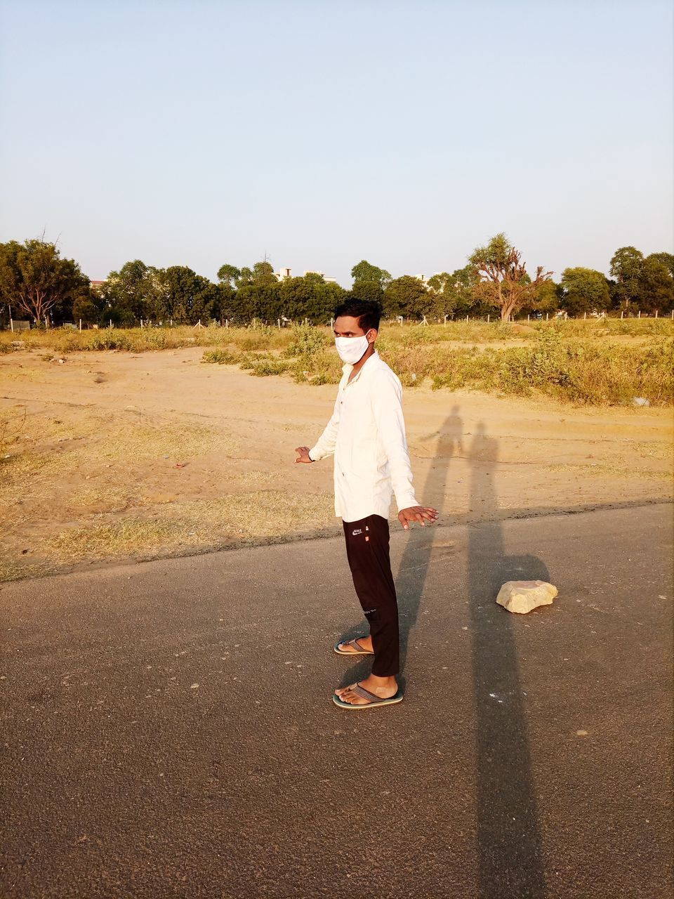 MAN STANDING ON ROAD AGAINST CLEAR SKY