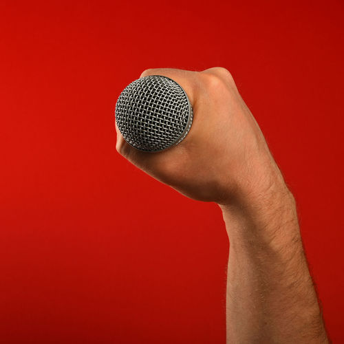 Close-Up Of Cropped Hand Holding Microphone Against Red Background