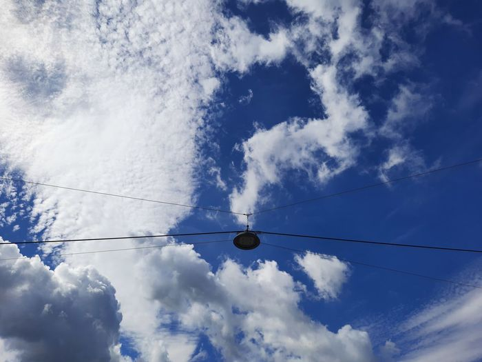Low angle view of silhouette cables against blue sky