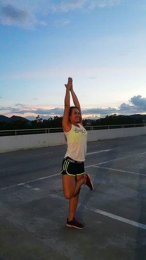 Full length of woman doing yoga on road against sky
