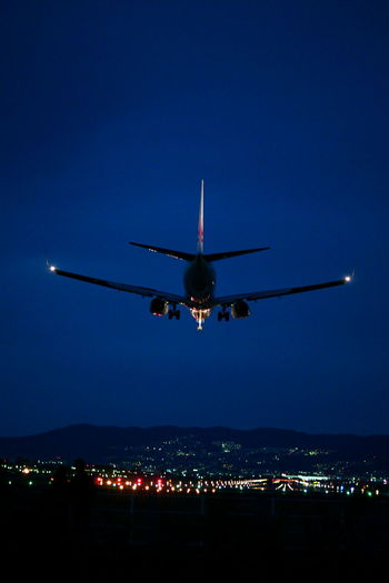 Low angle view of airplane flying against sky at night