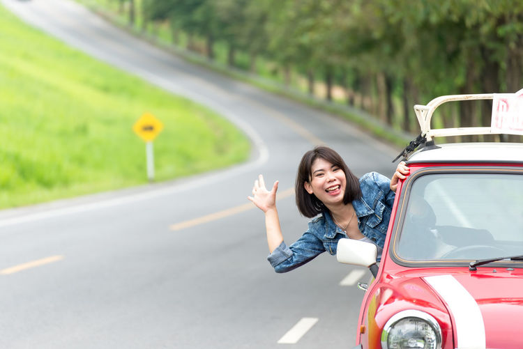 Portrait of smiling woman on road in city