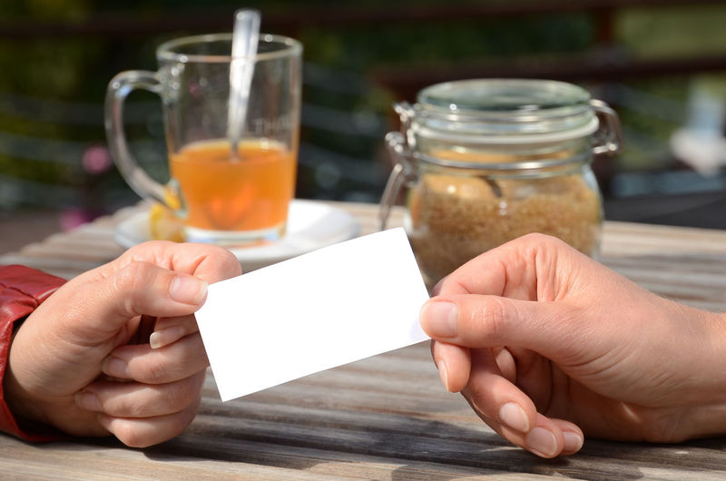 Cropped Image Of People Holding Blank Tag At Table