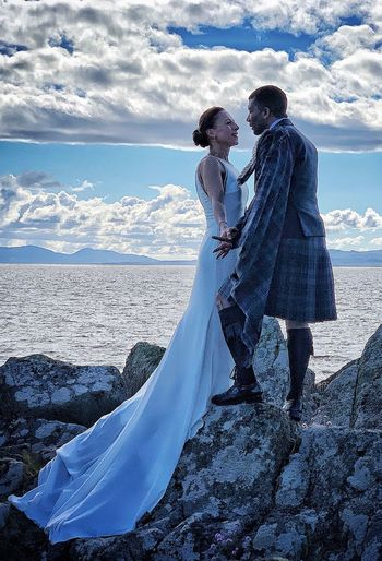 Couple standing on rocks by sea against sky