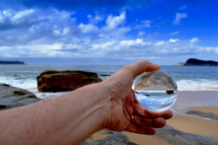 Cropped hand of person holding crystal ball at beach